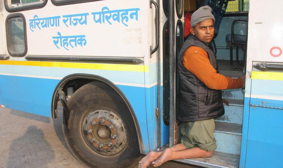 Image showing a person trying to climb into a public bus in India.