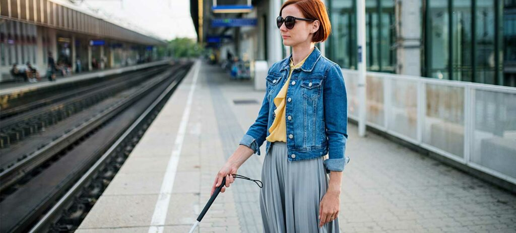 a blind young lady wearing black sunglasses and holding a white cane at a railway station.