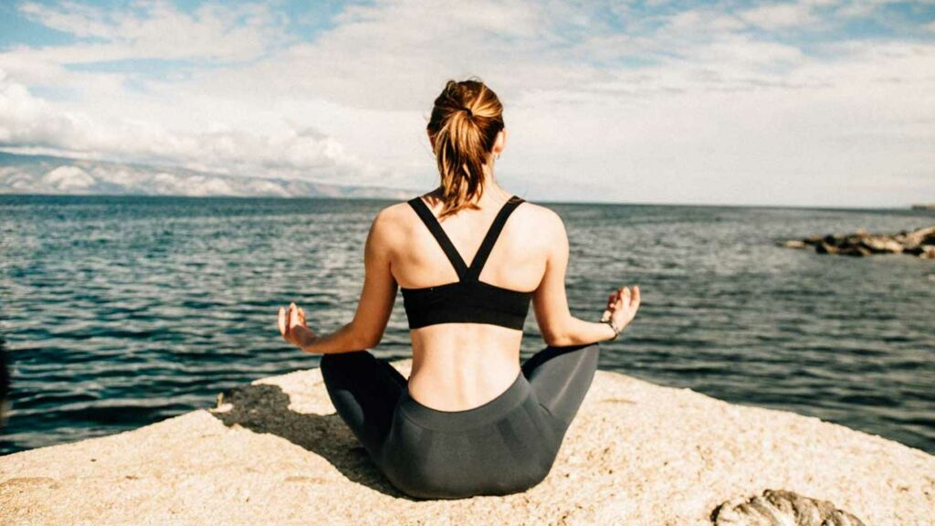 a woman sitting on a rock doing meditation on seashore.