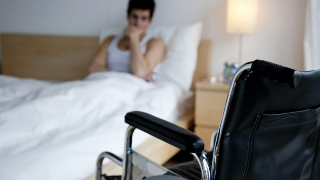 A man sitting on bed staring at his wheelchair. Physical disability can affect mental health of a person.