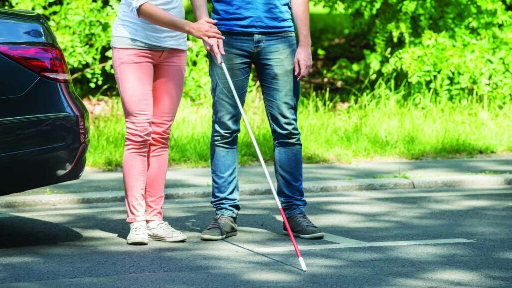 a blind man learning to use using white cane with the help from a women instructor.